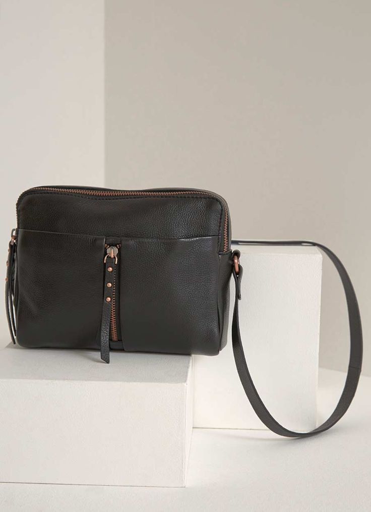 This black leather cross body bag will become your go to bag for the season ahead. Featuring contrasting rose gold hardware and an outer zip. This stylish piece is perfect for keeping valuables close at hand. Bag measures 18cm/7in in height, width across middle is 22cm/8.5in, base width is 7cm/3in.