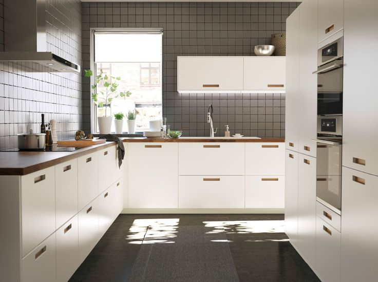 A large white kitchen with walnut worktops.