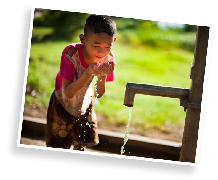 A child in Cambodia drinks safe water from a pump installed by Cambodian Hope Organization.