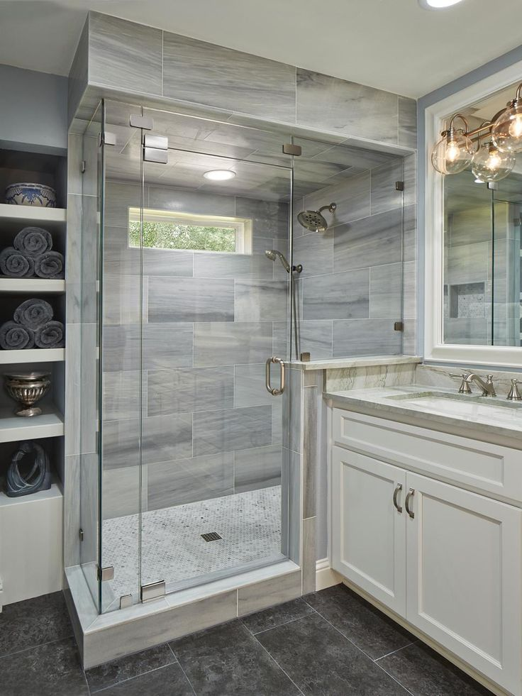 A mix of stone, marble and tiles create a rich and elegant master bathroom. The shower is Lena white marble with a floor of small circular tiles, the vanity a quartzite material, and the floors a darker-toned limestone.