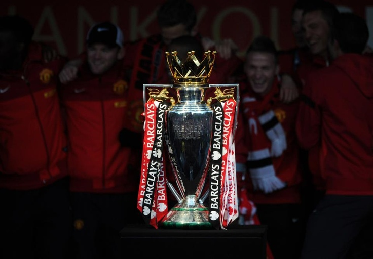 The Premier League trophy is displayed as celebrations continue outside Manchester Town Hall