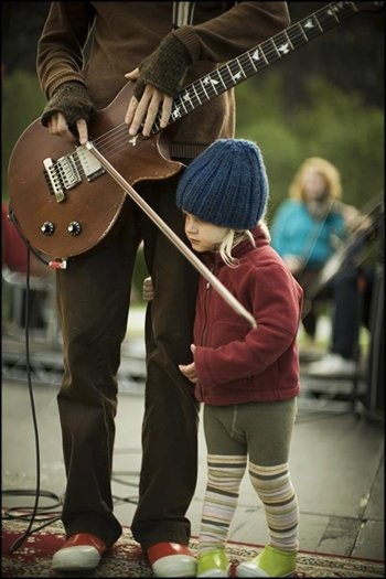 Lead singer of Sigur Ros, Jonsi, in concert with bandmate's child.