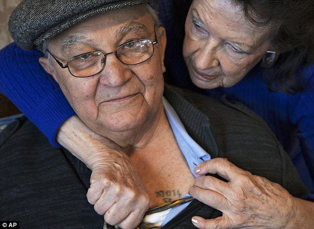 Survivor: Bessie Mittelman, 82, helps show the number tattooed on the chest of her husband Manny Mittelman, 88. He is one of the few Auschwitz survivors to have a chest tattoo. After the stamp system was replaced prisoners were tattooed on their arms
