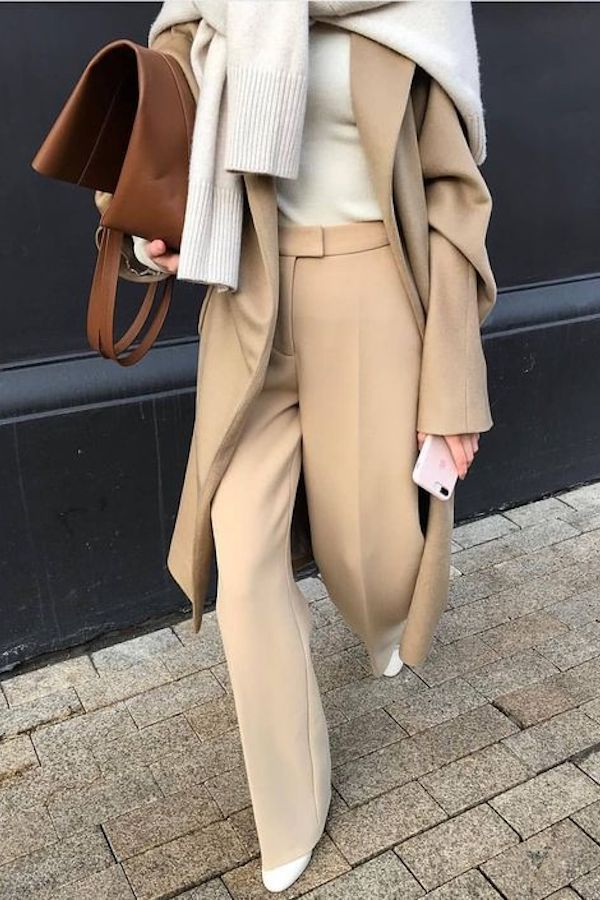 Minimaler klassischer neutraler Look. Kamelhose, beigefarbener Pullover und langer Kamelmantel.