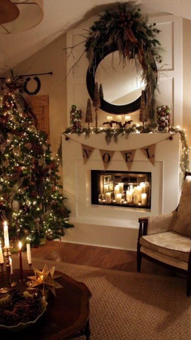 Christmas decorated fire place.  Love all the candles and lights. Don't like the mirror with the shrub on top, so would simplify it and only have mirror or wreath.
