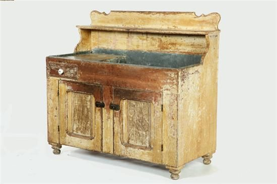 "DECORATED DRY SINK. Indiana, late 19th century, poplar. High back with one drawer, two doors, on turned feet and retaining a zinc lining. Old mustard over cream paint decoration. Wear and some losses. 44 1/2""h. 48""w. 21 1/2""d."