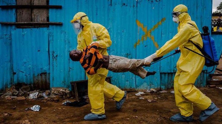 Un jeune garçon de 8 ans est transporté par le personnel médical du centre de traitement de Monrovia, au Liberia, le 5 septembre 2014. Potentiellement atteint du virus Ebola, il attendra plusieurs heures avant d'être ausculté.