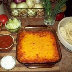 Serve this hot dip made with seasoned ground beef, refried beans and cheese with crunchy tortilla chips and fresh taco-style toppings!