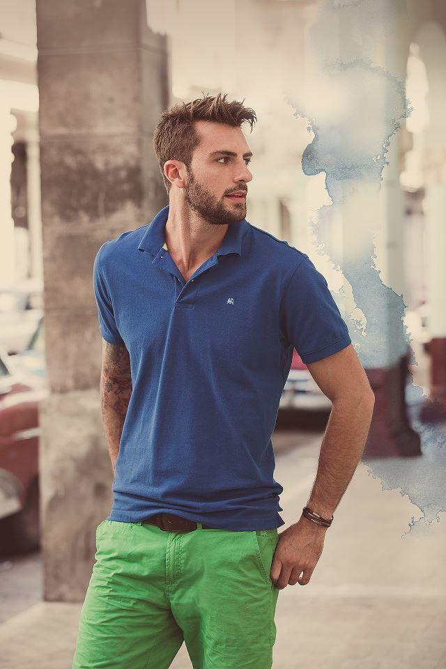 Elige una camisa polo azul y un pantalón chino verde para conseguir una apariencia relajada pero elegante.