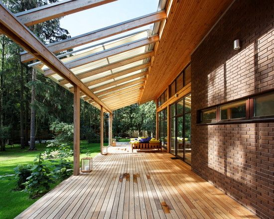 , Attractive Contemporary Porch With Glass Roof Extensions Also Wooden Deck Material Also Brown Bricks Wall Modern Windows Design Also Modern Exterior Wall Lamp Also Gorgeous Green Field And Pine Trees Garden: Glass Roofs for Cool House