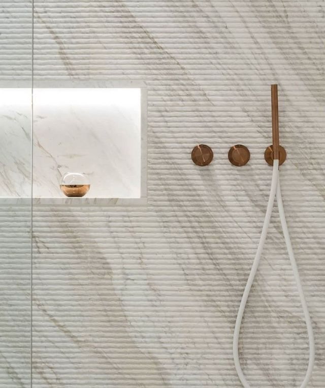 Bathroom with ribbed stone, shower with lighting niche and brass hardware accents.