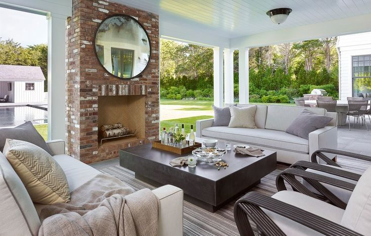 An outdoor sitting area continues the muted color scheme with a pair of track arm sofas by Dune, a custom concrete cocktail table designed by Scotti, and a couple of vintage Paul Frankl rattan armchairs. A salvaged train traffic mirror from JED Antiques hangs above the fireplace.