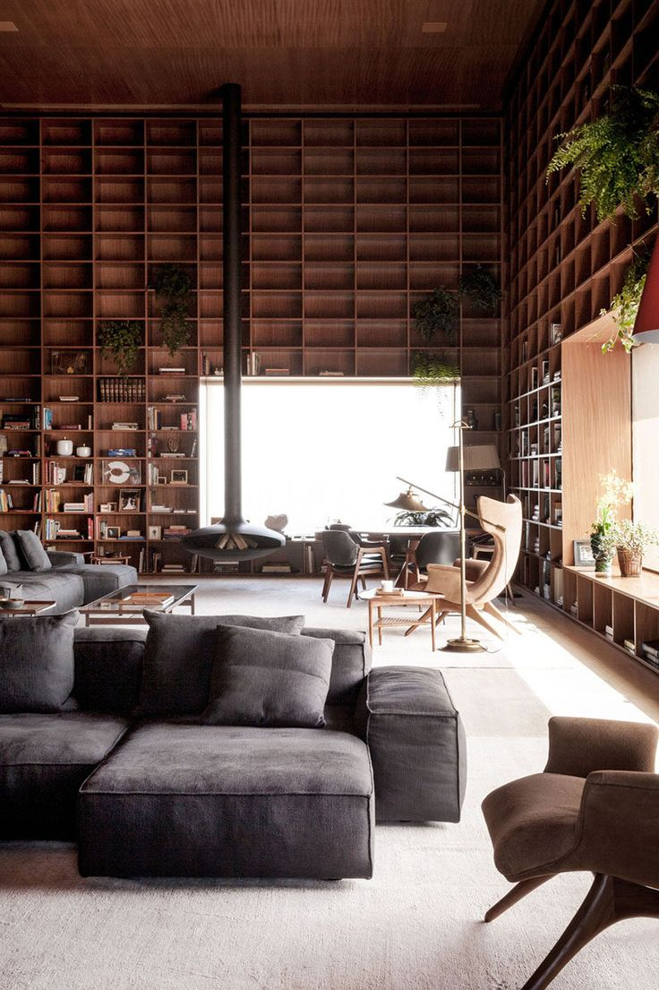 Studio mk27 design a double height room with floor-to-ceiling wooden shelves