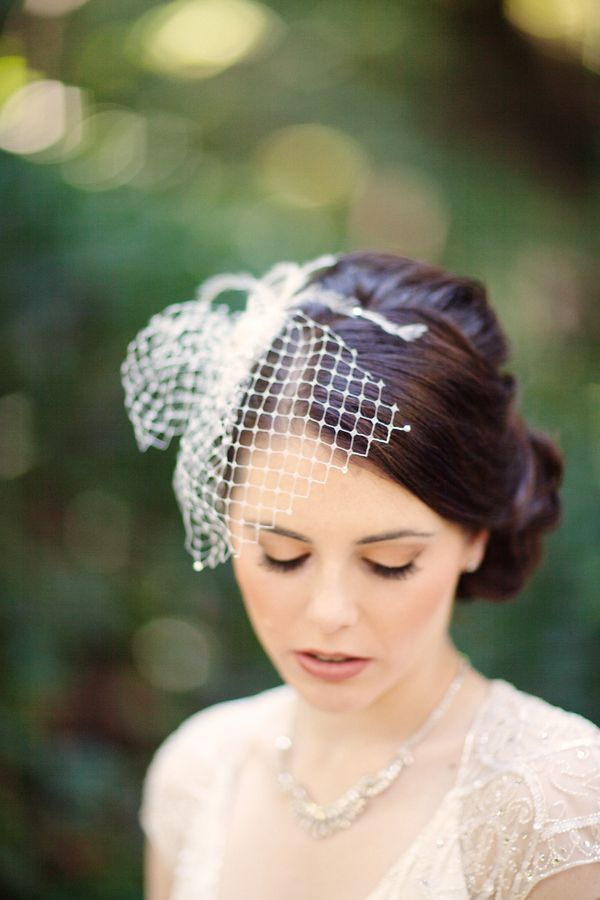 side curly bun -- perfect with birdcage veil...