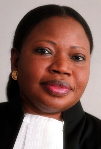 """Fatou Bensouda was born on January 31, 1961 in Banjul, Gambia. She is a Gambian lawyer who holds the title of being the first African and first woman to hold the International Criminal Court's role of Chief Prosecutor. She is Gambia's first international law expert in history - holding masters degrees in International Maritime Law and Law of The Sea. Bensouda was named one of """"100 of the Most Influential People in the World,"""" by Time magazine in 2012."""