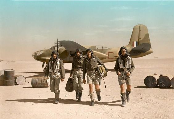 """IWM caption - """"The crew of Douglas Boston Mark III, W8376 'C', of No 24 Squadron, South African Air Force, walking away from their aircraft on an airfield in Libya after a sortie."""":"""
