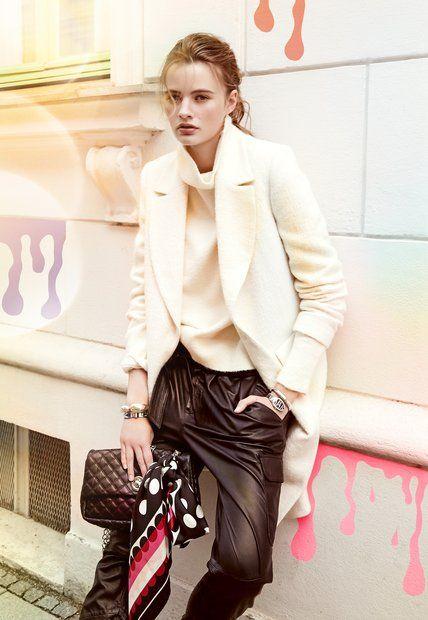 Deutsche Mode: Black & White. Lederhose und Strick-Rolli von Set. Darüber ein weißer Wollmantel und eine Tasche von Oui. Buntes Seidentuch von Codello. Schwarze Uhr von Bulgari. Emaille-Armspange von Hermès. Armspange in Silber von Pomellato