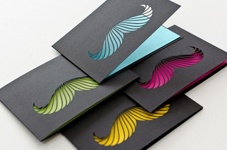 Stylish folded cards in black with a mustache cutted out of them and various beautiful colors.