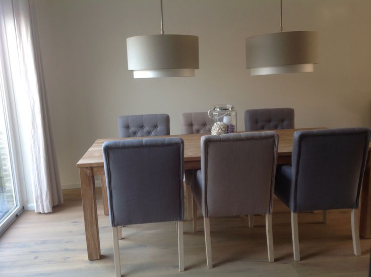 Landelijke eethoek met dubbele lampenkap en mooie gecapitonneerde stoelen.