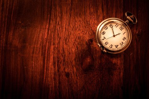Stock image of 'Vintage pocket watch on solid wood'