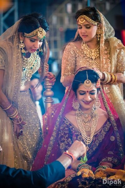 Sister of the Bride - Bride and her Sisters | WedMeGood | Bride in a Marsala Outfit with Polki Necklace, Maatha Patti and Jhumkas, Sisters in Gold outfits with Emerald and Polki Jewelry #wedmegood #indianbride #sisterofthebride #gold #marsala #indianwedding #lehenga #bridal