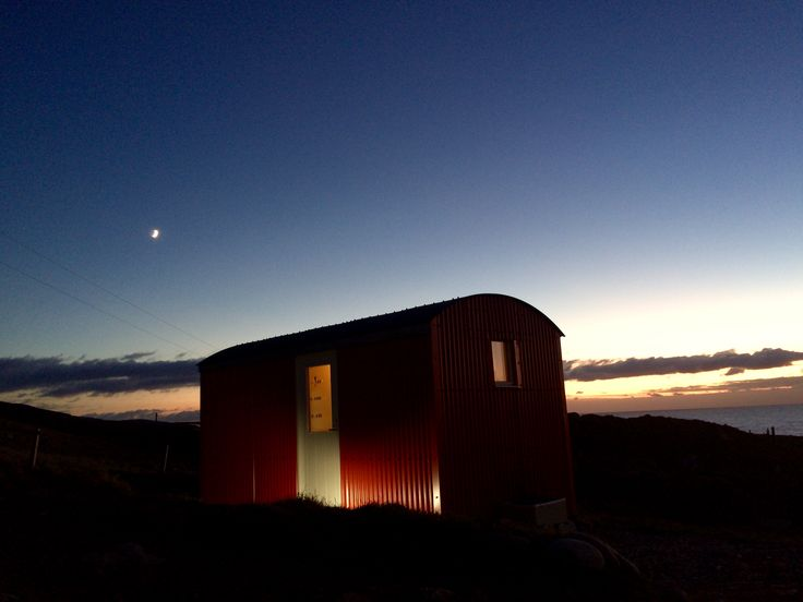 The Shepherd's Hut at twilight on a winter's evening. Located in a coastal village in the Hebrides, the hut has a lovely view out across the ocean. With no light pollution, the Night sky is full of stars and the Milky Way can be viewed on cloudless nights.