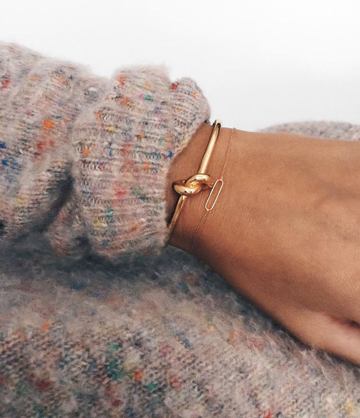 Under the cuff / Celine knot bracelet and delicate bracelets poke out from a cozy fall sweater: