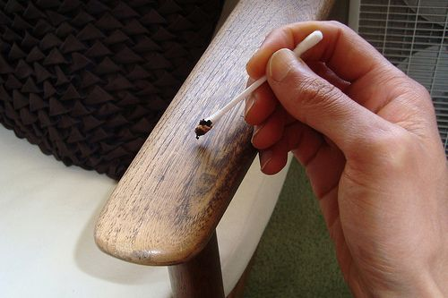 Cover scratches in wood furniture using used coffee grounds, applying with a cotton swab.