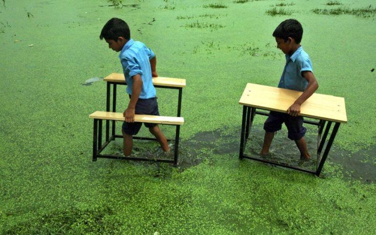 Jammu, Kashmir. Alcuni ragazzi salvano i banchi dall'alluvione trasportandoli a mano all'asciutto