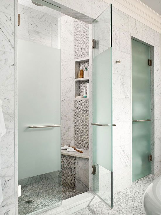 Create a fashionable seat that draws the eye inside your walk-in shower. This shower's interior boasts an arresting interplay of square and mosaic tiles that repeats down the face of the built-in bench, conveniently situated below a pair of toiletry niches. A solid slab of marble overhangs the bench base to magnify the seat's impact.