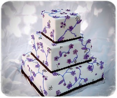 This wedding cake has three tiers of purple flowers and black ribbon ladder lines.