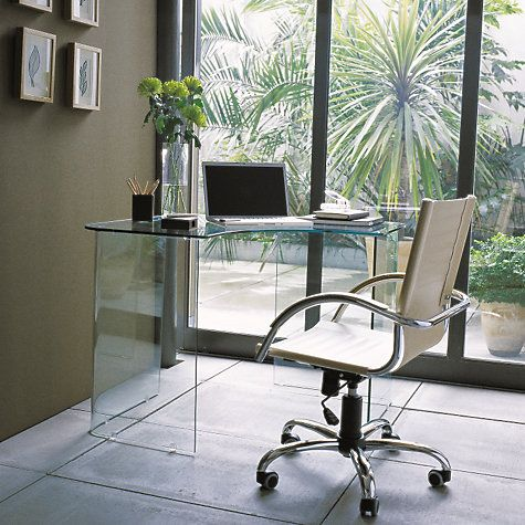 An all-glass corner desk with trestle that not only saves space, but creates the illusion of it because of its minimal structure and the way its transparency throws light.