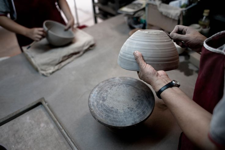 An artisan hand-finishes pottery at the Doi Tung Development Project
