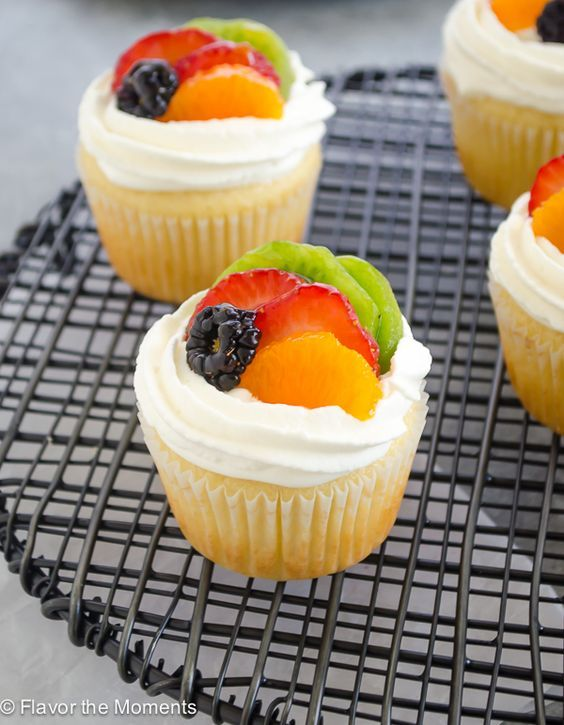 Fruit Tart Vanilla Cupcakes are light vanilla cupcakes filled with pastry cream and topped with fresh fruit and whipped cream topping.  They're the ultimate spring dessert! @cloverstornetta