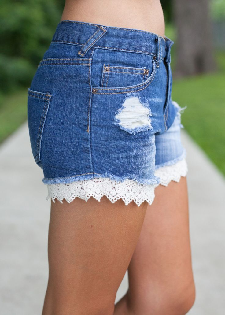 "Distressed denim shorts with frayed edges and lace hem. 80% Cotton, 20% Polyester Model: Mackenzie is 5'4"", wears a size 2/4, and is shown wearing a size small."