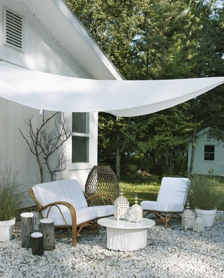 To give a bare back garden a focal point, create an outdoor lounge area with basic gravel. A simple white sunsail over head pulls everything together. A painted tree stump in a white lacquer creates a unique textural table and detailed lanterns add an exotic touch.