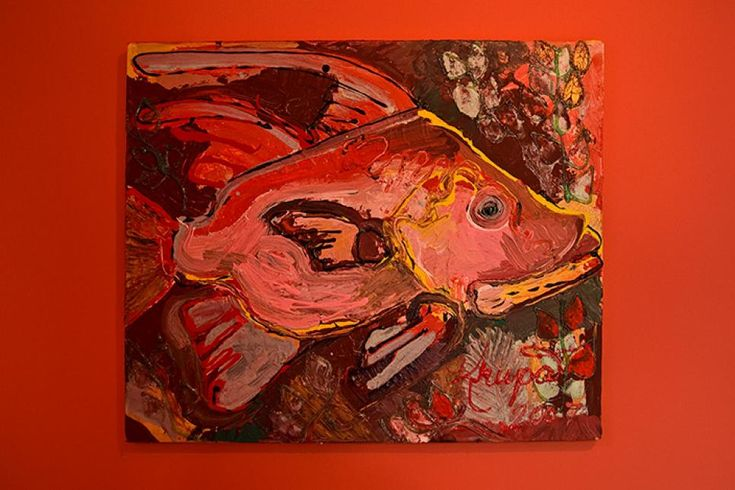 """A vibrant mixed-media painting, """"Hogfish Local Talent,"""" by local artist Stacie Krupa, adds one more shot of color to the space. Past the door leading into the garage is a closet containing a custom wine storage system from California Closets. Directly across from the wine closet is a door into a storage area beneath the stairs."""