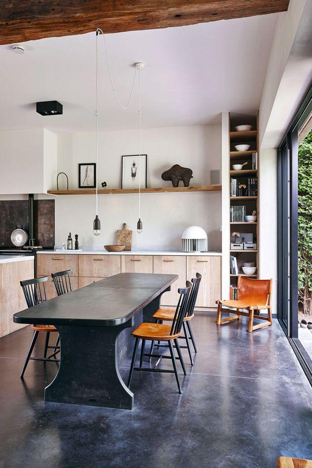 De open keuken in de voormalige schuur geeft je extra ademruimte. De betonnen vloer en de leistenen tafel brengen de natuur in huis. Ook hier is elk object een 'beeldhouwwerk' zoals de Malinese buffel boven het aanrecht.