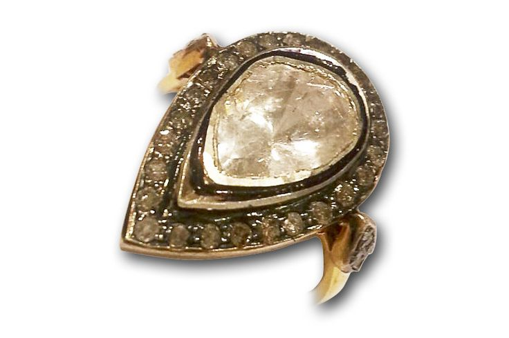 18 KARAT GOLD RING WITH BLACK DIAMONDS AND A PEAR-SHAPED INDIAN POLKI CENTRE DIAMOND.