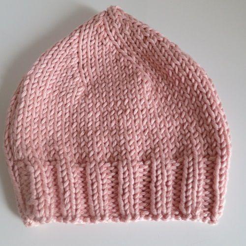 Tricot: petit bonnet rose en spirale.