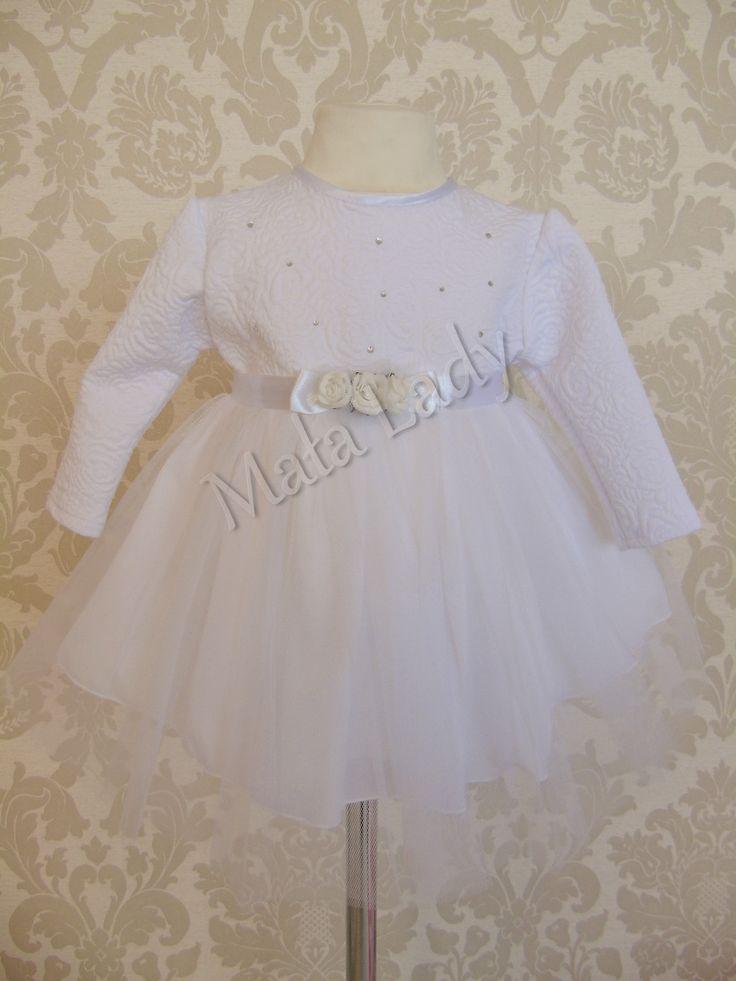 Sukienka róża do chrztu wykonana z białej dzianiny żakardowej w kwiaty połączona z podwójnym tiulem. Całość odszyte płótnem bawełnianym oraz podszewką. Sukienka posiada długi rękaw oraz kryty zamek z tyłu keracji. Atłasowa szarfa wiązana z tyłu pozawala na dopasowanie kreacji do ciała.