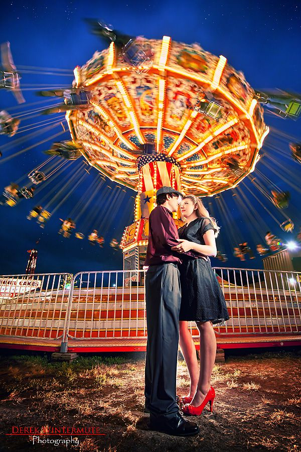 Sweet kisses beside a carnival ride.. A romantic filled engagement photo!