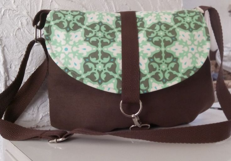 This is a super cute messenger style bag with the flap in a contrasting designer fabric by Amy Butler. A smaller sized bag but still big enough to fit all your essentials.It can be worn as a shoulder bag or across the body if you need to be hands free. It features an adjustable strap, spring hook closure and inside pocket.