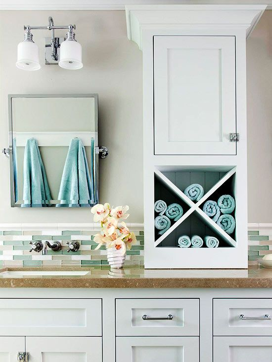 For an easy and inexpensive bathroom storage solution, consider retrofitting an existing vanity with a storage unit placed on the countertop. Here, a slender but versatile piece of cabinetry sits between the vanity's two sinks, providing open and closed storage at arm's length. The cabinet was topped with crown molding to give it a built-in look.