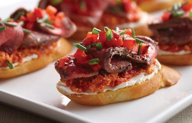 GRILLED NEW YORK STRIP CROSTINI'S: ~ From Omaha Steaks. ~ Omaha Steaks Strip Steaks help make this easy yet sophisticated recipe for Grilled New York Strip Crostinis a real winner. Simply spread roasted red pepper pesto on a French baguette, place the freshly grilled steak on top, add a dollop of cream cheese and garnish with peppers for this high-class, low-fuss sandwich - See more at: http://www.omahasteaks.com/servlet/recipe/grilled-ny-strip-crostini#sthash.n2xsR6j0.dpuf
