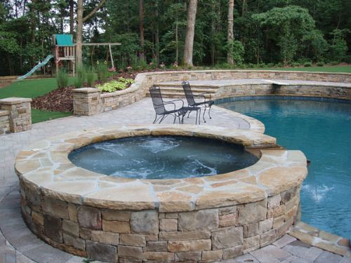 Tumbled Cobblestone Concrete Paver Pool Deck With Stone Faced Spa Seating Bench Walls Columns