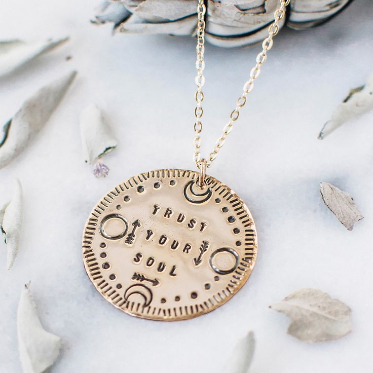 """Make a statement with this inspirational quote necklace. The necklace says  """"trust your soul"""" and has a moon and arrow design around the text."""