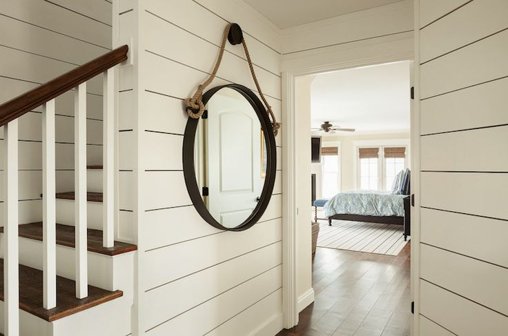 Entrance to bedroom features rope captain's mirror hanging on tongue and groove paneled walls.