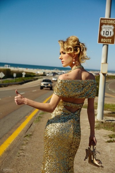 A lady in a ballroom gown on the highway with her thumb out, heels in hand?