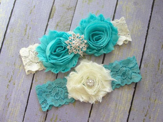 Wedding Garter Set This beautiful bridal garter set features ivory and dark aqua rosettes with crystal embellishments. The lace is in the colors ivory